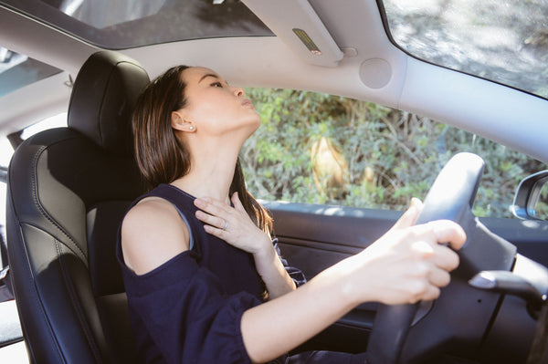 Woman devoted to K-beauty influenced holistic skincare habits sitting in driver seat of car stretching out neck and nexercising for smooth healthy skin