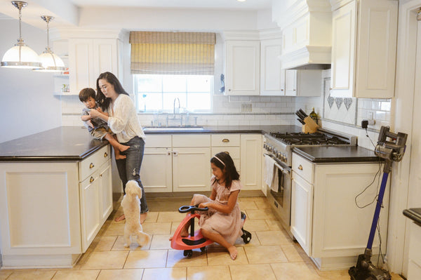busy asian mom engaged in holistic skincare life hacks with one toddler boy, little girl and small dog looking busy and distracted in kitchen