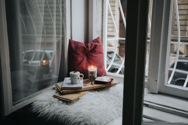 cozy corner insider of house next to window with candle and pillow set up for an at-home retreat as part of K-beauty influenced holistic skincare habits and rituals