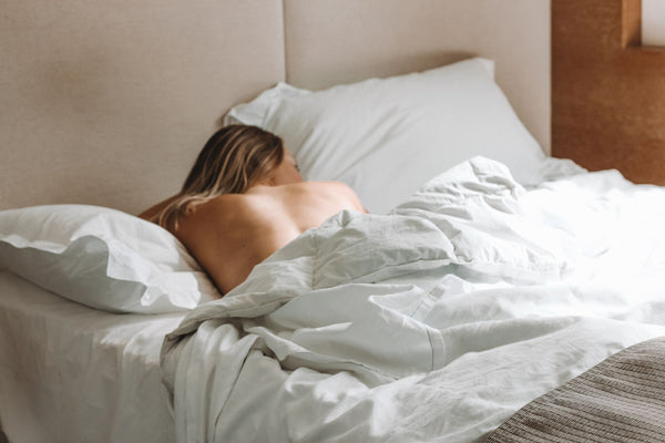 woman sleeping naked in bed catching up on some beauty sleep which is essential for good skin as part of K-beauty influenced holistic skincare habits and rituals