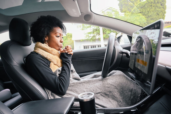 woman in car during the cold winter season with a blanket over her knees and the heater turned off to protect her skin as part of K-beauty influenced holistic skincare habits and rituals