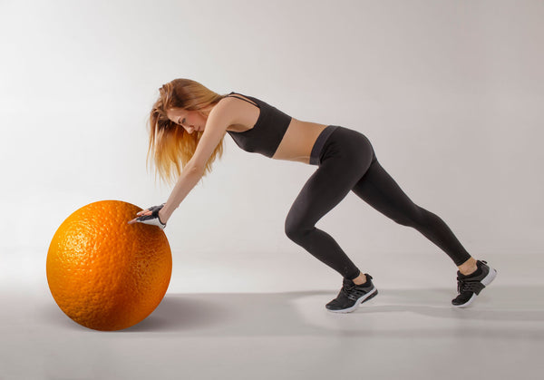 picture of woman pushing an orange representing cellulite encouraging developing a K-beauty influenced daily holistic skincare regimen that works for your unique brand of cellulite