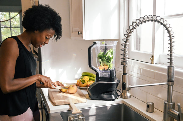 Woman in kitchen cutting up fruit and vegetables to juice in her blender as part of K-beauty influenced holistic skincare habits and rituals
