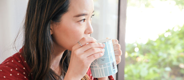 woman drinking detoxifying tea to cleanse and detox as part of K-beauty influenced holistic skincare habits and rituals