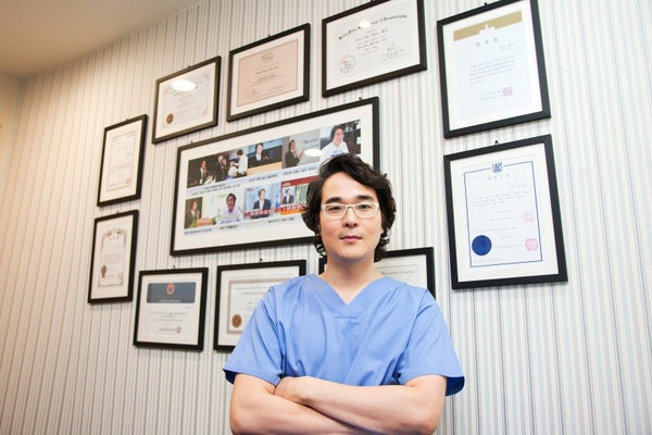 Dr. Choon-Shik Yoon, Korean certified dermatologist and K-beauty skincare expert, in scrubs against a wall being interviewed by SeoulofSkin, a K-beauty inspired holistic skincare brand