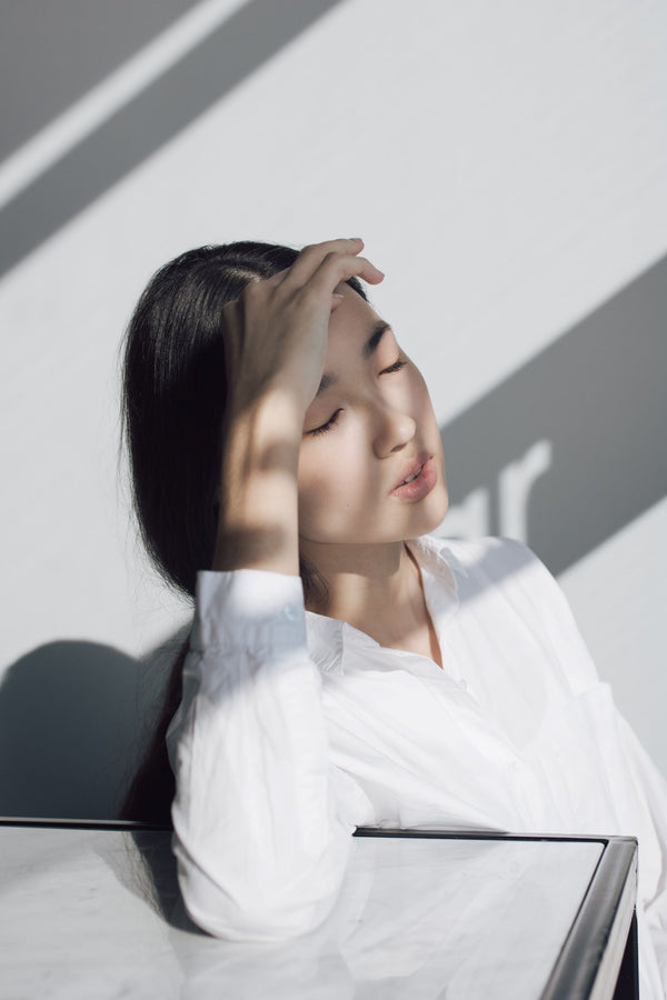 Asian woman in white blouse leaning against desk with hand on forehead and eyes closed in light and shadow symbolizing the differences between dry and dehydrated skin as part of K-beauty influenced holistic skincare habits and rituals