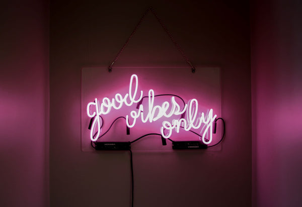 "pink neon sign in cursive saying ""good vibes only"" symbolizing the importance of empathy to maintain positive energy as part of K-beauty influenced holistic skincare habits and rituals"