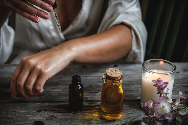 woman wearing gray robe dropping essential oil onto her arm with dropper next to candle as part of K-beauty influenced holistic skincare habits and rituals