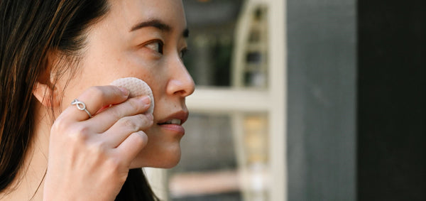 asian woman exfoliating her facial skin with an glycolic acid pad as part of K-beauty influenced holistic skincare habits and rituals