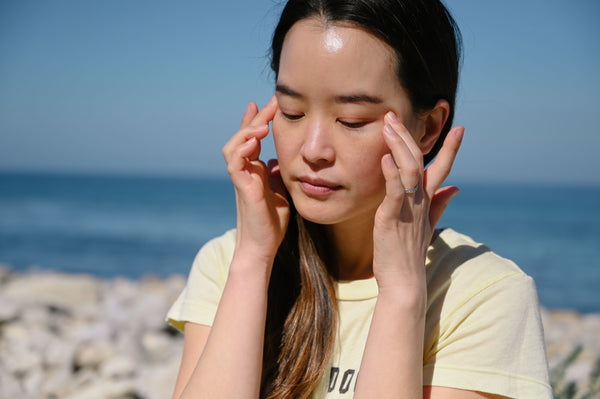 asian woman using fingers to massage her eye skin are as part of K-beauty influenced holistic skincare habits and rituals