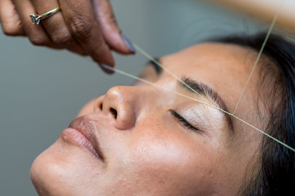 woman with eye closed getting her eyebrows threaded as part of K-beauty influenced holistic skincare habits and rituals