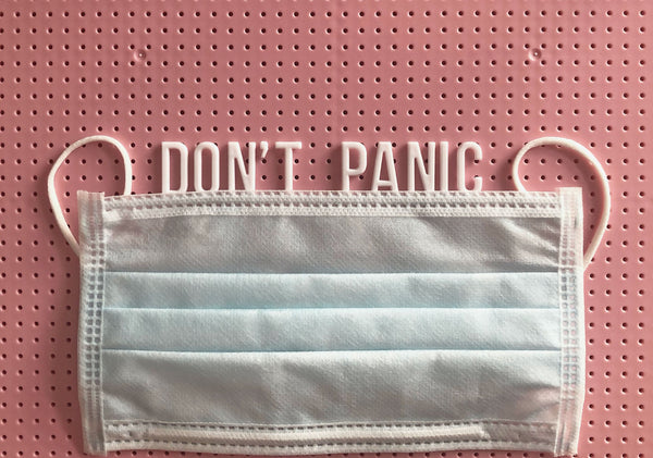 "image of protective mask against pink background with the message ""don't panic"" symbolizing the need to wear masks and the skincare issues that relate to that"
