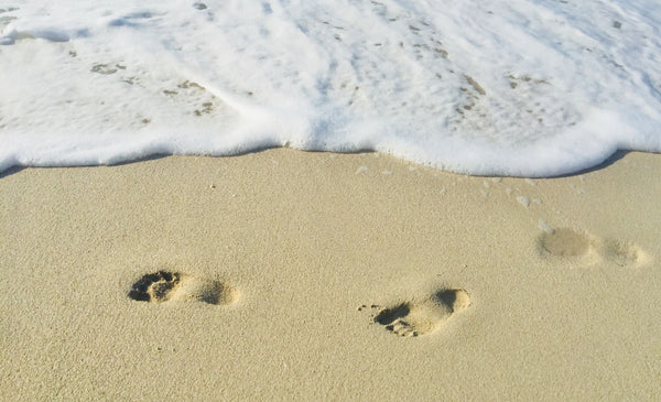 footprints on sand at beach symbolizing the importance of footcare as part of your daily skincare routine as part of K-beauty influenced holistic skincare habits and rituals