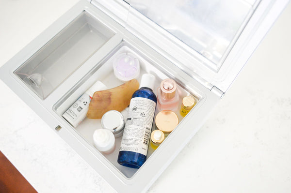 Open cosmetics fridge with various skincare products stored within as part of K-beauty influenced holistic skincare habits