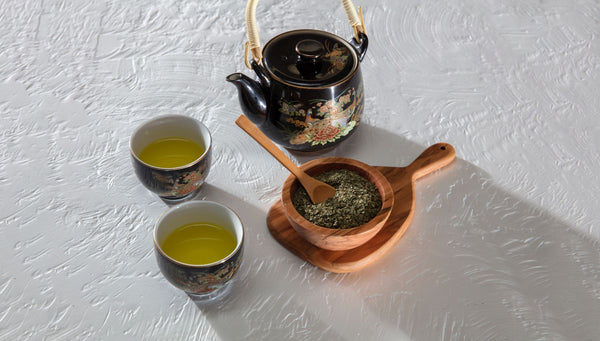 two cups of green tea next to kettle and tea leaves showing that green tea is beneficial for skin and should be consumed daily as part of K-beauty influenced holistic skincare habits and rituals