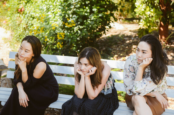 three beautiful diverse women devoted to K-beauty influenced holistic skincare habits sitting on bench at South Coast Botanical Garden leaning on face to show bad habits of skincare