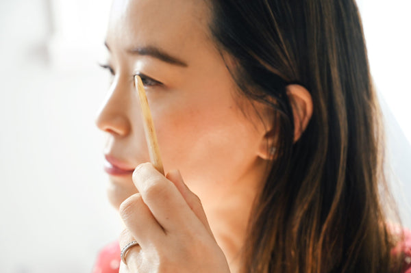 Woman with gua sha tool scraping and massaging her cheek area as part of K-beauty influenced holistic skincare habits