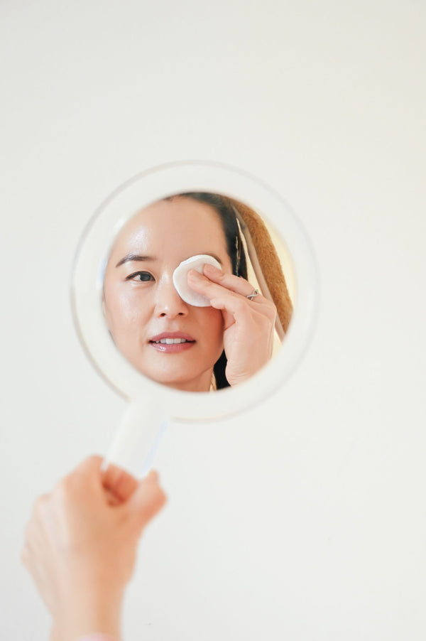 Woman in dog Halloween costume holding up mirror and removing eye makeup properly as part of K-beauty influenced holistic skincare habits