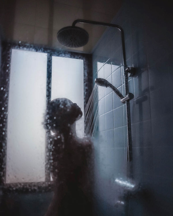 woman in shower with hard water which is bad for skin and hair and should be fixed as part of K-beauty influenced  holistic skincare habits