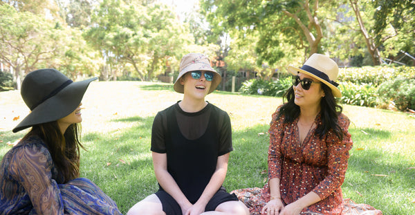 Three women sitting on lawn in UCLA campus under the sun wearing sun protective stylish hats as part of K-beauty influenced holistic skincare habits