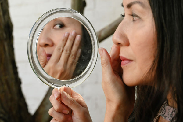 explaining-peptides-in-skincare-products-symbolized-by-woman-looking-into-mirror-to-check-for-wrinkles