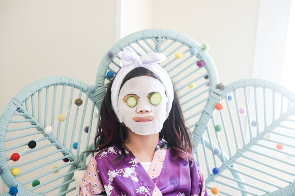 8 year old girl with a face mask and cucumbers on her eyes engaging in good skincare habits early as part of K-Beauty influenced holistic skincare experiences