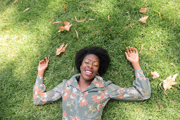 Beautiful African American woman with glowing skin closed eyes and smile lying on grass at UCLA campus with fallen leaves looking happy as part of K-beauty influenced holistic skincare practice