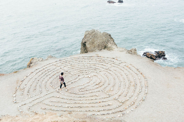 woman on beach next to the sea walking a stone labyrinth symbolizing the question of whether life is a maze or a labyrinth