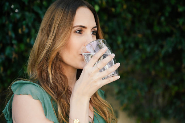 Lauren Eckstrom drinking a glass of water and remembering to keep hydrated from the inside out in green dress as part of K-beauty influenced holistic skincare rituals and habits