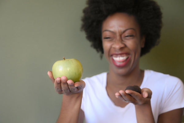 charity-holding-apple-and-chocolate-and-reexamining-her-sugar-intake-for-healthy-skin-as-part-of-soffli-skincare-rituals