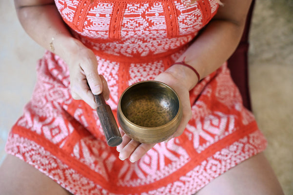 woman's hands holding small meditation sound bowl as she engages in loving-kindness mediation as part of K-beauty influenced holistic skincare habits and rituals