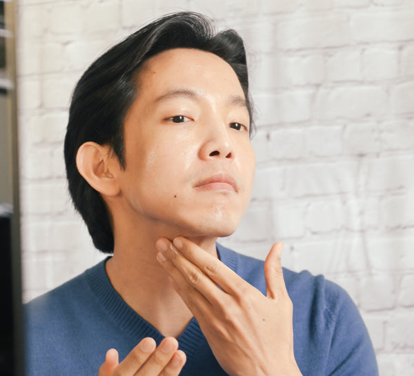 asian man looking in mirror applying serum as part of a simple man's skincare routine as part of K-beauty influenced holistic skincare habits and rituals