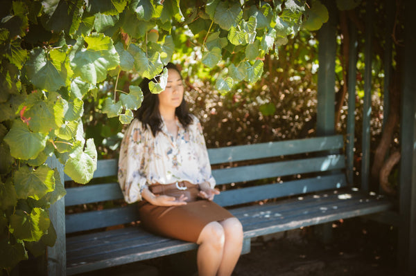 Woman meditating on bench in the park under tree