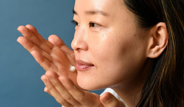 woman applying just the right amount of moisturizer to her face and neck as part of K-beauty influenced holistic skincare habits and rituals
