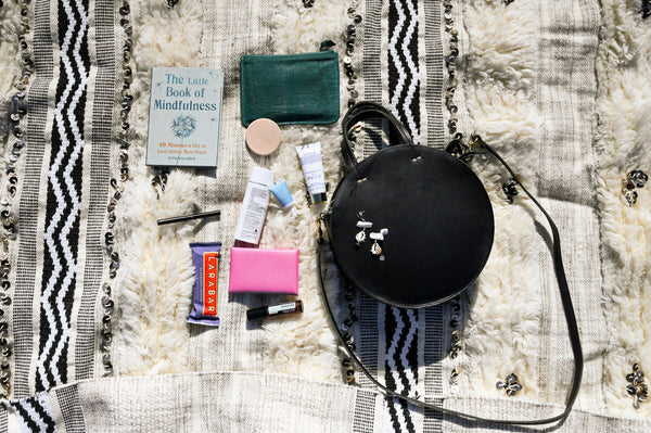 inside contents of skincare junkie's bag which includes sunscreen, lip balm and hand cream, etc., laid out on a blanket as part of K-beauty inspired holistic skincare habits and rituals