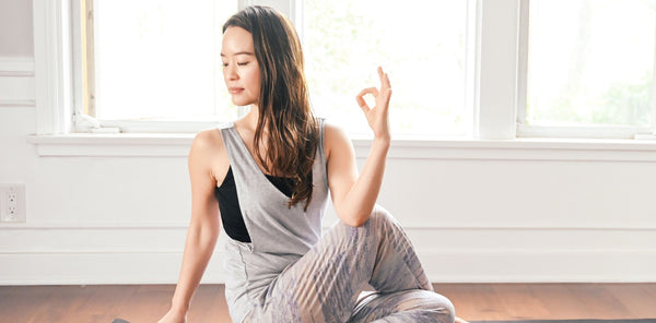 woman in house against window practicing yoga as part of K-beauty influenced holistic skincare habits