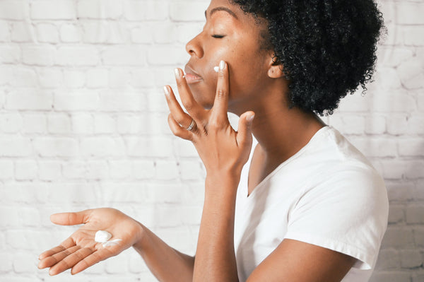 african american woman in white t-shirt against white brick wall applying moisturizer to oily skin as part of K-beauty influenced holistic skincare habits and rituals
