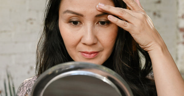 asian woman touching forehead and looking closely into mirror examining her wrinkles as part of K-beauty influenced holistic skincare habits and rituals