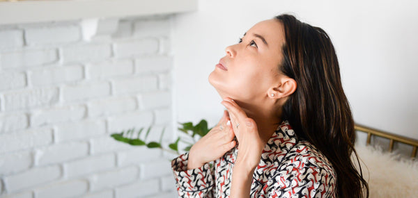beautiful asian woman applying moisturizer to her neck as part of k-beauty influenced holistic skincare practice