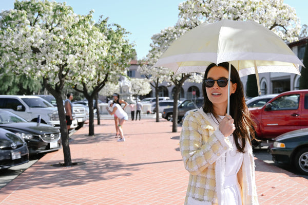 Asian woman in yellow jacket wearing sunglasses and holding a light yellow parasol for sun protection as part of K-beauty influenced holistic skincare habits and rituals