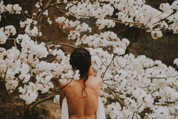 naked woman's back against white cherry blossom tree symbolizing the importance of balanced pH levels in your body as part of K-beauty inspired holistic skincare habits and rituals