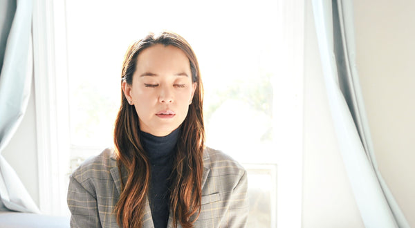 Asian woman with closed eyes engaging in face relaxation mediation to prevent RBF (resting bitch face) as part of K-beauty influenced holistic skincare habits