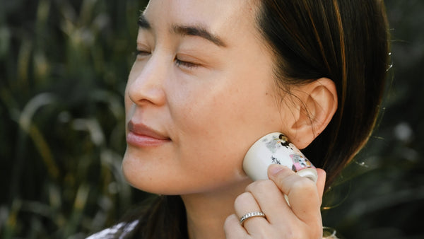 asian woman with eye closed using white sake glass to massage her jawline as part of K-beauty influenced holistic skincare habits and rituals