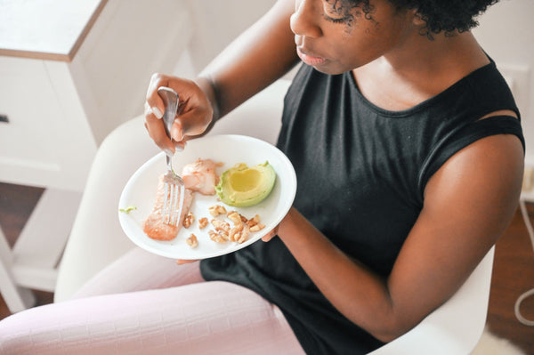 woman eating avocado, walnuts and salmon, the 3 skincare super foods as part of K-beauty influenced holistic skincare habits and rituals