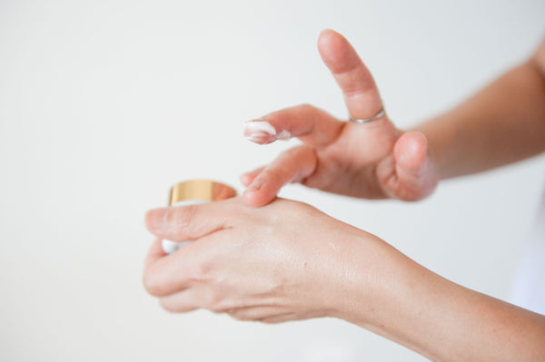 Woman hand applying eye cream and moisturizer onto hand as part of steps 3 and 4 of K-beauty influenced holistic skincare morning 6-step routine