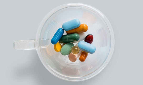 cup full of colorful pills and supplements symbolizing the question of which oral supplements should be taken for skincare health as part of K-beauty influenced holistic skincare habits and rituals