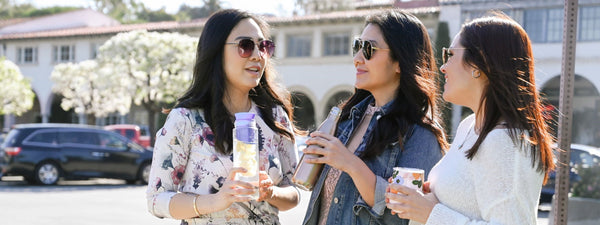 three women with water bottles drinking water as part of a water challenge for healthy skin as part of K-beauty influenced holistic skincare habits and rituals