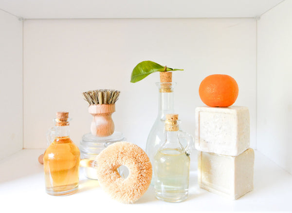 glass cosmetic jars, bars of clean soap and an orange and green leaf symbolizing the importance of building sustainability into our skincare practices