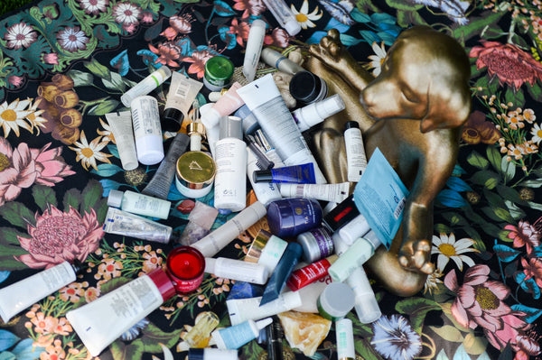 pile of various skincare products on colorful blanket symbolizing the question of whether you need to regularly switch out skincare products for efficacy as part of K-beauty influenced holistic skincare habits and rituals