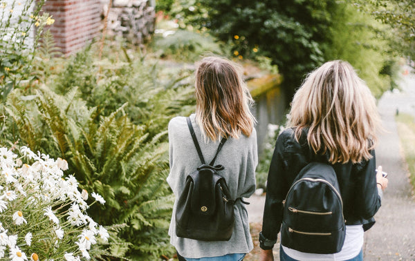 two teenage girls with backpacks on walking down a road symbolizing the importance of teen skincare as part of K-beauty influenced holistic skincare habits and rituals